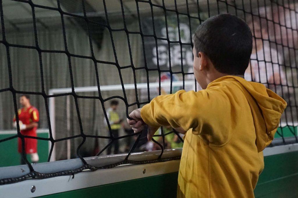 Kleiner Junge sieht beim Fußball spielen zu.